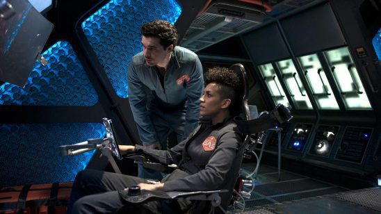 Two characters in The Expanse looking at a screen.