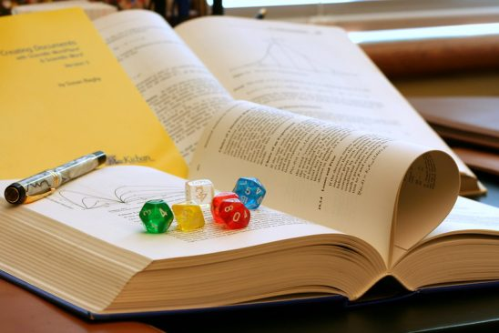 A book with pen and dice on top of it.