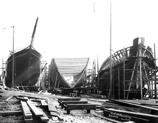 A photo of sailing ships in the process of being built.