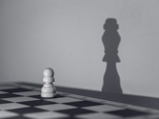 A chess pawn casting the shadow of a queen.