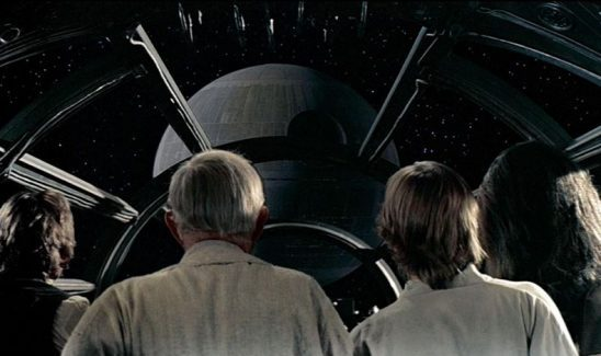 Luke, Obi-Wan, Han, and Chewy gaze at the Death Star as their ship is sucked into it