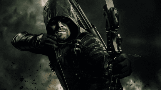 A man in a dark hood aims an arrow