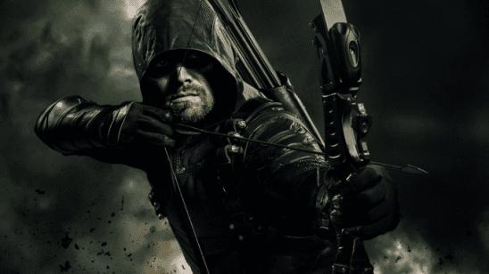 A man in a dark hood aims an arrow