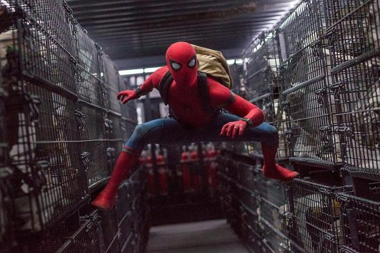 Spider-Man balancing between two rows of cages.
