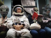 Three aliens sit next to an astronaut