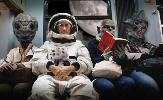 Three aliens sit next to an astronaut
