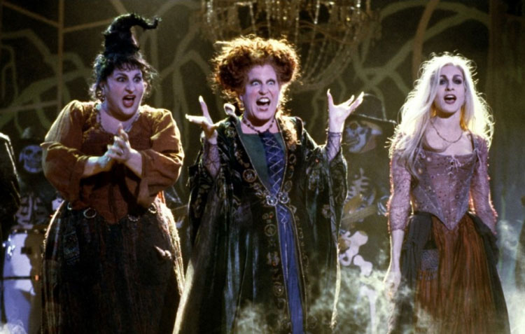 The three Sanderson sisters from Hocus Pocus singing on stage