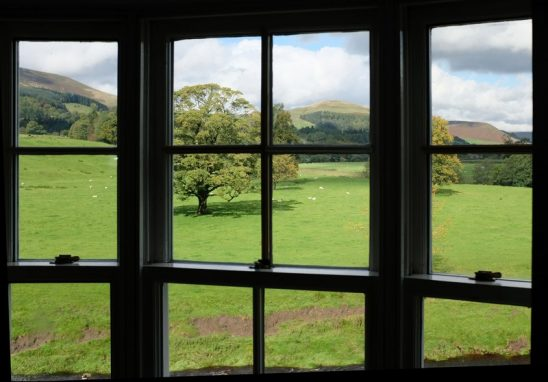 A landscape of rolling grassy hills shows through a window
