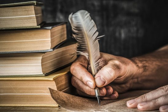 Hand holding quill pen writes on aged paper next to a pile of books