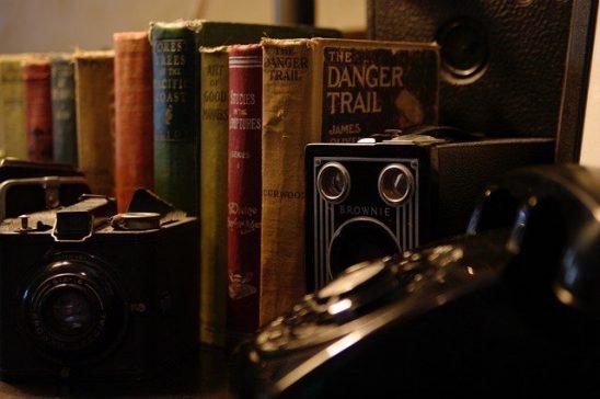 A shelf with books and camera equipment.