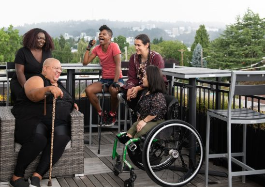 Five disabled people of color sit on a deck laughing, with high-rises in the background.