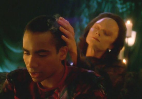 A young black man writes as an alien woman sits behind him with her hand on his head and her eyes closed