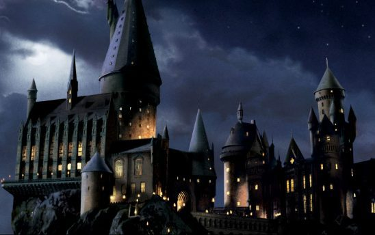 A still from the Harry Potter movies of Hogwarts castle at night.