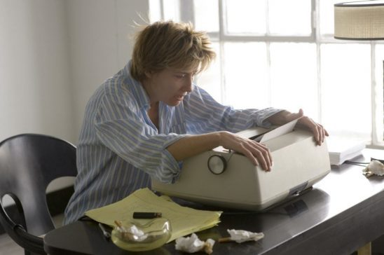 A rumbled white woman with short hair stares is dismay at her typewriter.