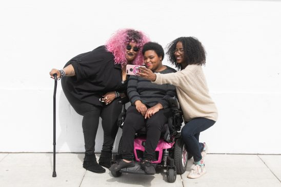 Three disabled Black friends taking a selfie together against a white wall.