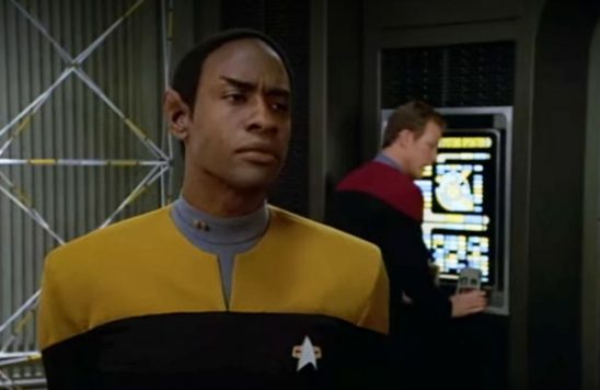 Tuvok from Voyager stands on the holodeck with Paris behind him at the controls.