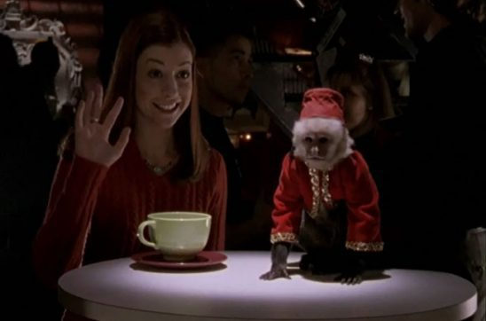 In a dark room, red-haired Willow holds her hand up in a hello as she sits at a table next to a small monkey in an outfit