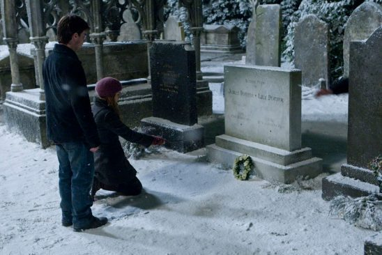 Harry and Hermione in a snowy graveyard, looking at the grave of Harry's parents