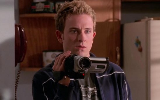 A young white man stands in a kitchen holding up a video camera