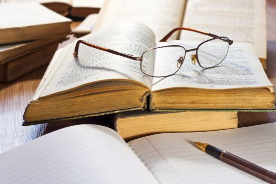 Glasses sit on an open book next to an open notebook with a pen on it
