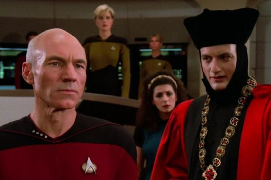 Picard and Q standing on the bridge
