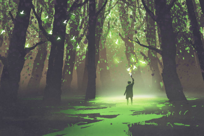 A man stands in a green glowing clearing in the forest reaches upwards to touch some glowing birds in flight