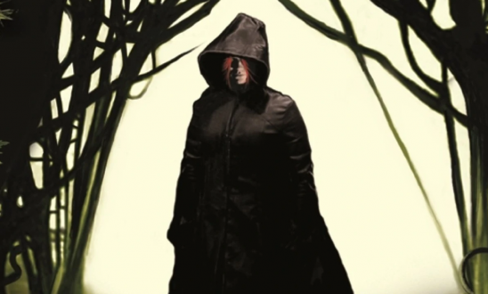 A hooded figure with red hair.